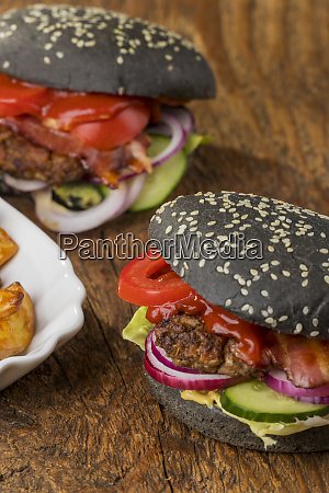 closeup of black hamburgers on wood