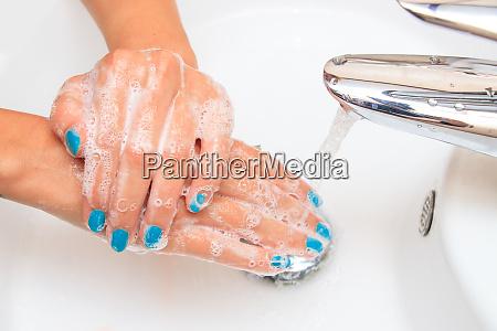 female hands under running water in