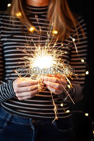 hands holding burning sparklers