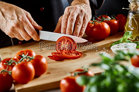 hands of a male chef slicing