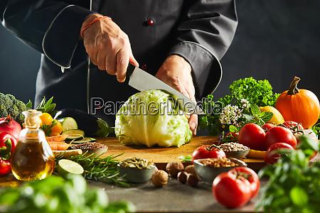 chef slicing through a fresh green