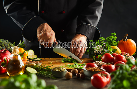 chef dicing fresh herbs with a
