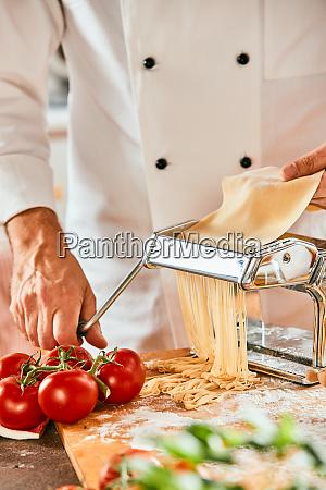 chef cutting raw dough on a