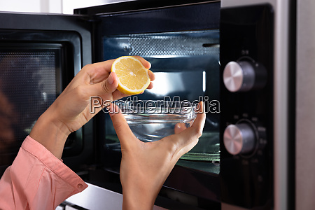 womans hand squeezing halved lemon in