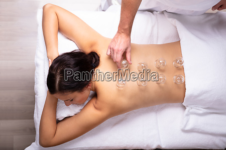 woman receiving cupping treatment on her