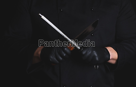 cook in black latex gloves sharpens