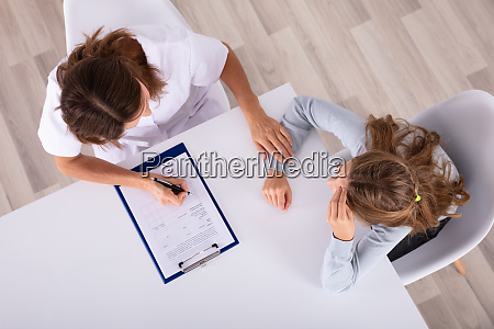 doctor sitting with girl patient in