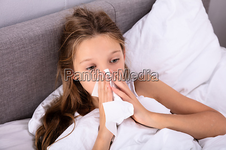 girl blowing her nose with handkerchief