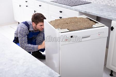 technician repairing dishwasher