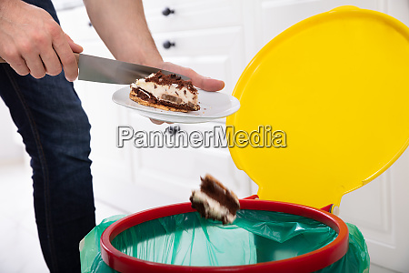 man throwing cake in trash bin