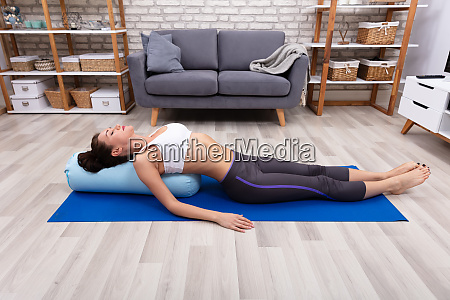 young woman practicing yoga with bolster