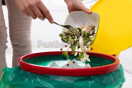 woman throwing vegetables in trash bin