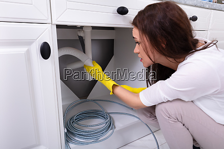 woman cleaning clogged sink pipe