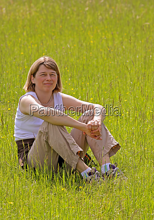 woman squats in the grass