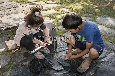 children cleaning utensils outdoors in shimla