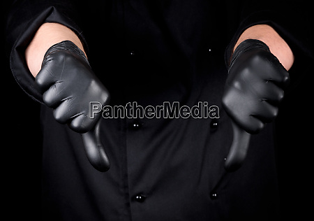 chef in black latex gloves shows