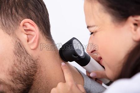 doctor checking skin on mans neck