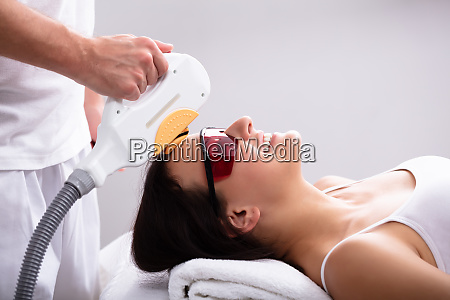 beautician giving laser depilation treatment to