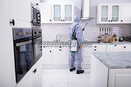 worker spraying insecticide chemical in kitchen