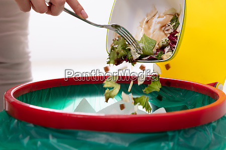 woman throwing vegetables in trash bin