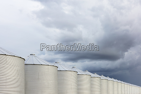 rows of grain silos stormy skies