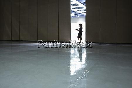 businesswoman standing in a doorway between