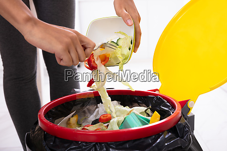 woman throwing salad in trash bin