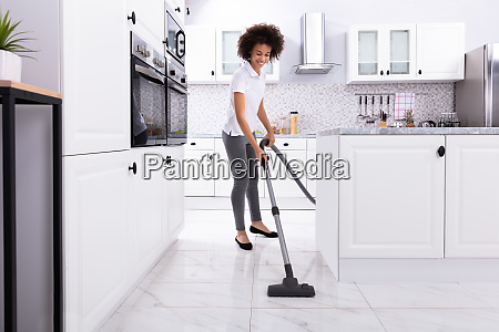 woman cleaning kitchen floor with vacuum