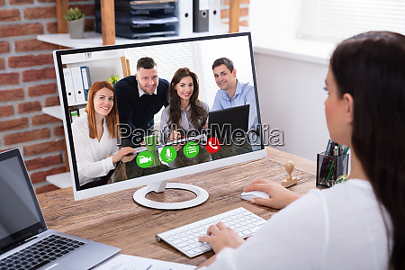 businesswoman videoconferencing with her colleagues on