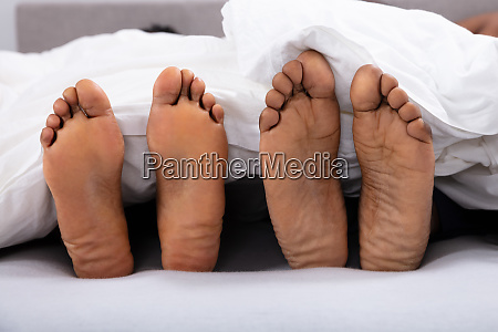 close up of couples bare feet