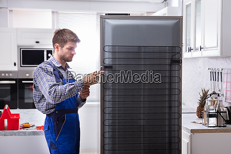 serviceman in overall working on fridge
