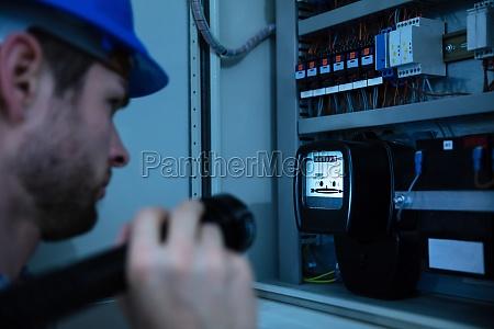 electrician examining a fuse box