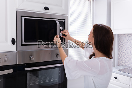 woman using microwave oven