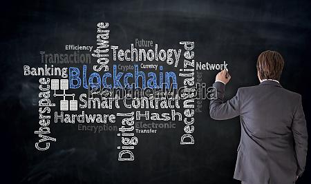 businessman writes blockchain cloud on blackboard