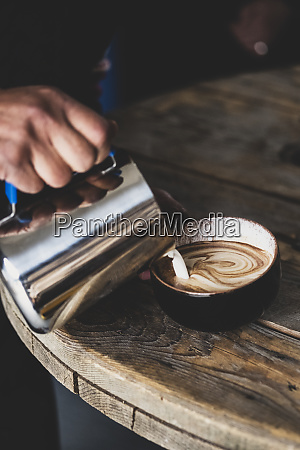 close up of barista pouring milk