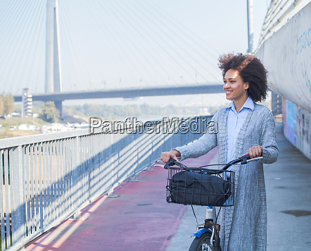 afro young woman with bicycle enjoying