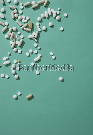 pills scattered on green background