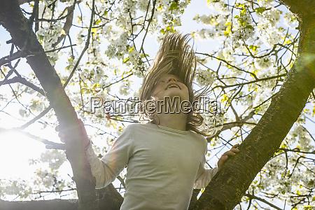 playful girl climbing spring tree