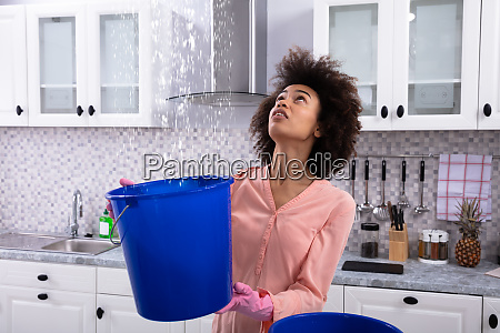 woman collecting water leaking from ceiling
