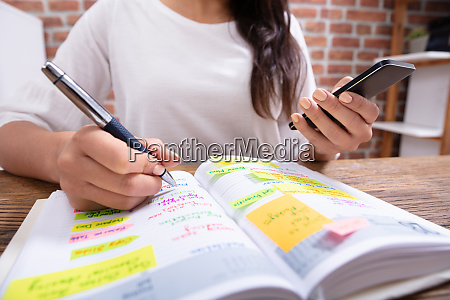 businesswoman holding cellphone writing schedule in