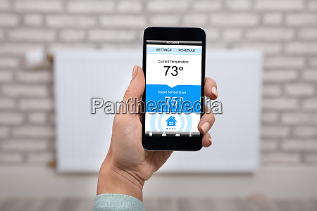 woman operating thermostat using smartphone