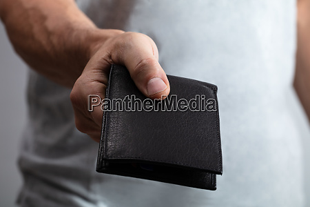 persons hand holding black wallet