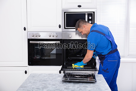 male janitor cleaning oven in kitchen