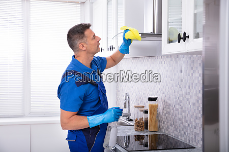 male janitor cleaning cooker hood