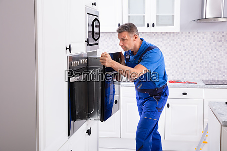 technician in overall installing oven
