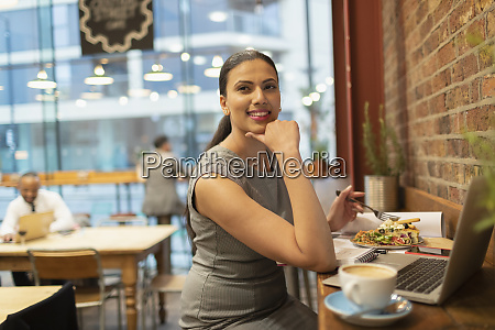 confident businesswoman eating lunch and working