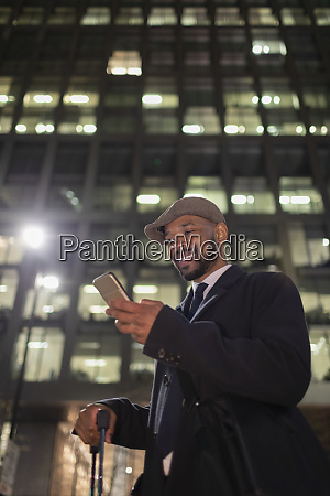 smiling businessman with smart phone standing