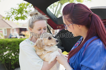 lesbian couple and dog in driveway