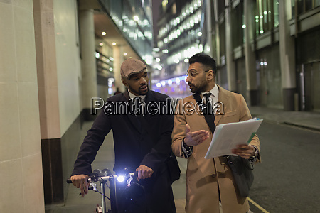businessmen with bicycle and paperwork walking