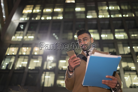 businessman with paperwork and smart phone